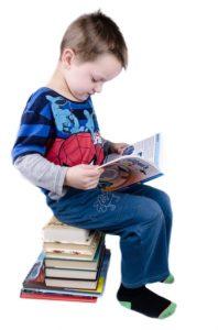 foto di bambini assorto nella lettura seduto su una pila di libri