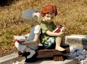 Statuette di bambini che leggono all'aperto