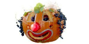 zucca di halloween addobbata in modo buffo come fosse un pagliaccio