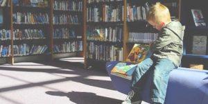 foto di un ambiente interno di una biblioteca per ragazzi con un bambino seduto su divanetto che legge